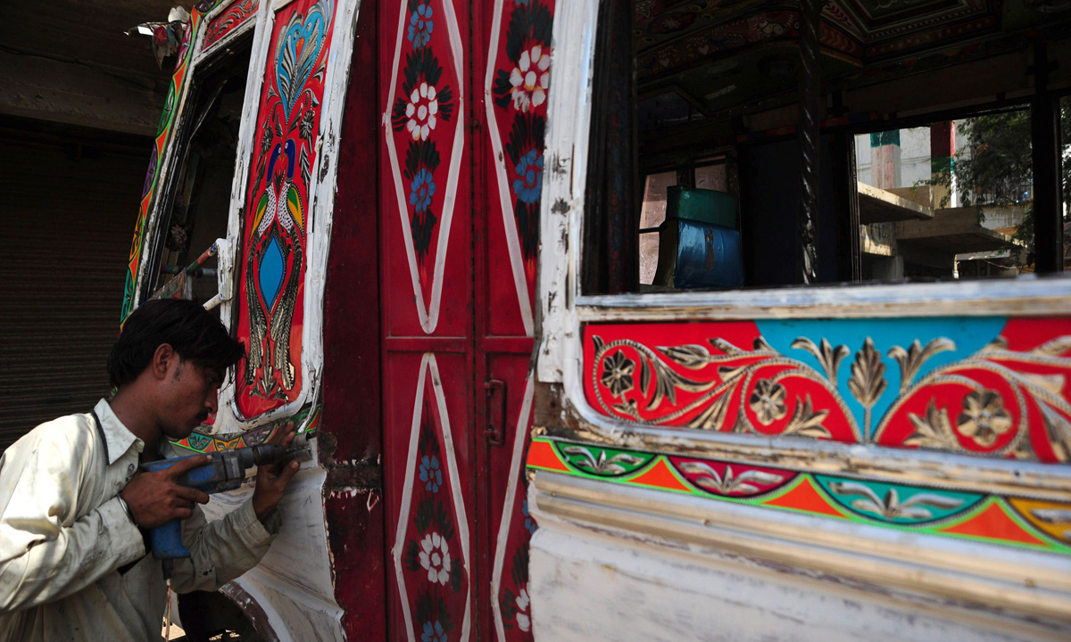 A labourer works on the exterior of a passenger mini bus in Karachi.