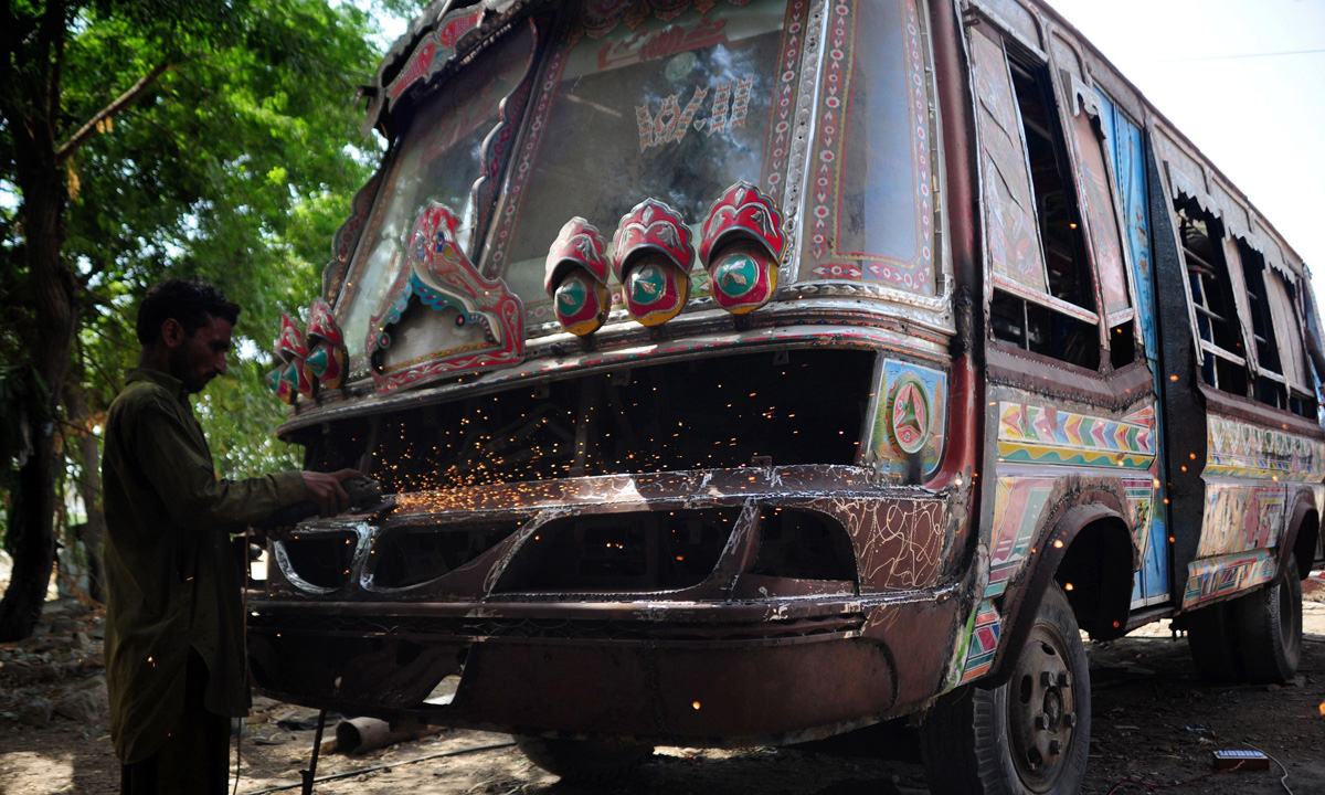 A Pakistani labourer works on the body of a passenger mini bus in Karachi.