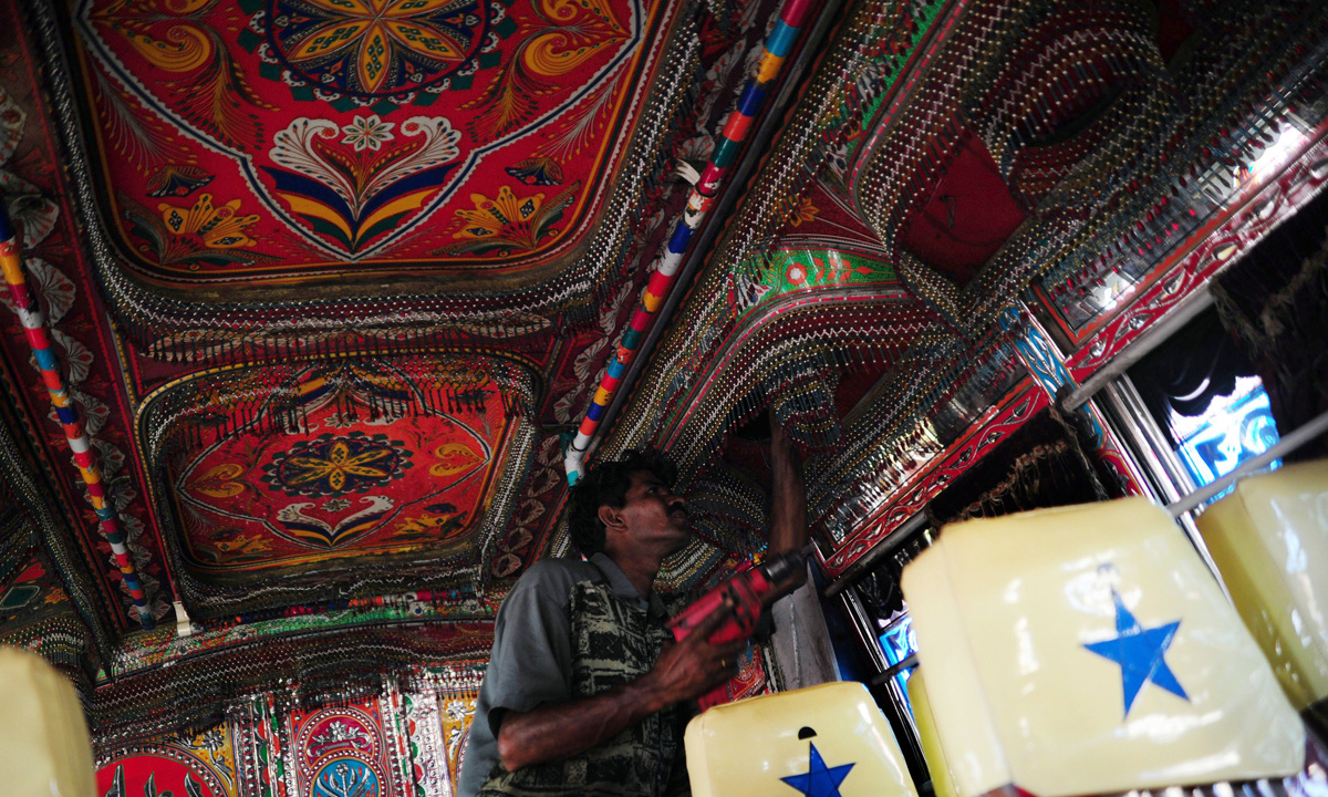A labourer decorates the interior of a passenger mini bus in Karachi.