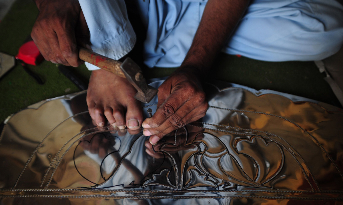 A Pakistani artisan carves a decorative design onto a thin metal sheet to be put together and fixed on the body of a mini passenger bus in Karachi.