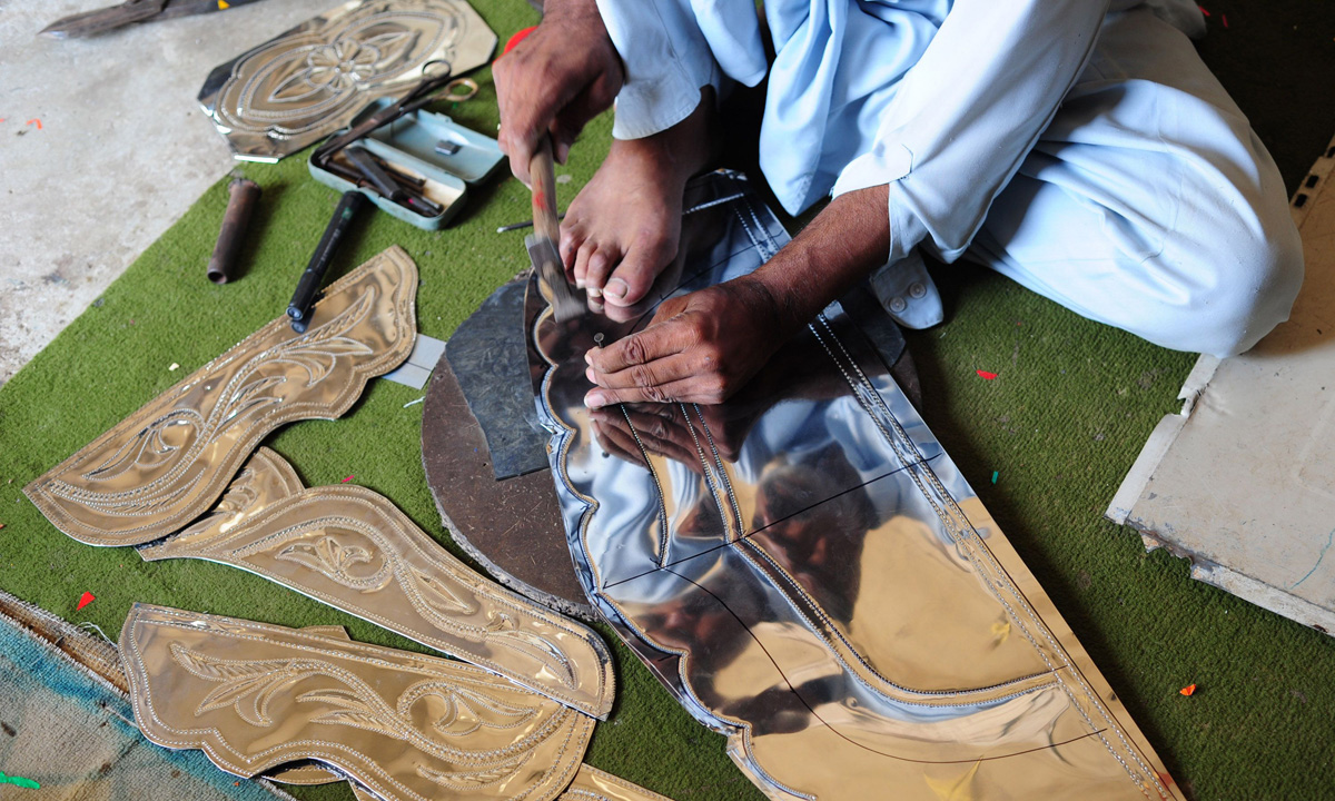 A Pakistani artisan carves a decorative design on a thin metal sheet to be put together and fixed on the body of a mini passenger bus in Karachi.