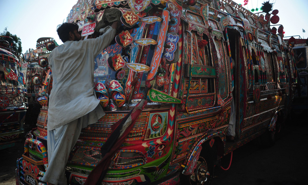 A cleaner dusts a deccorated mini passenger bus in Karachi.