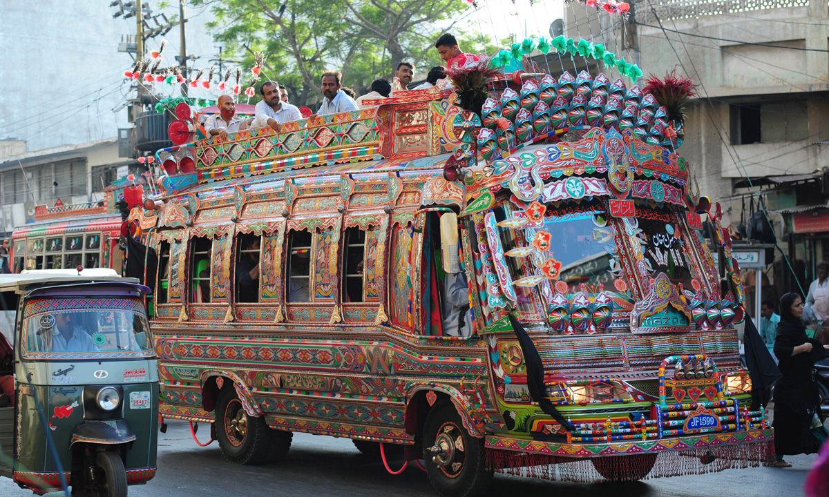 Pakistani passengers travel on a decorated mini passenger bus in Karachi.
