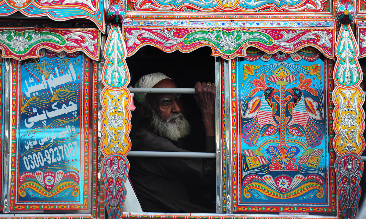 A passenger travels in a decorated mini passenger bus in Karachi.