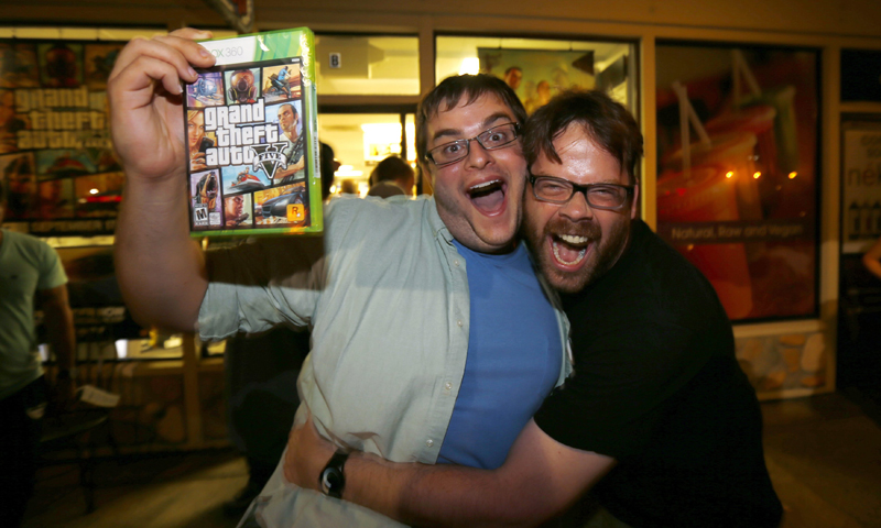 "Gaming enthusiast Casey Riffel holds up his copy of the latest release of ""Grand Theft Auto Five"" as he gets a hug from animator Michael Petterson after midnight at a Game Stop gaming store in Encinitas, California September 17, 2013. — Reuters Photo"