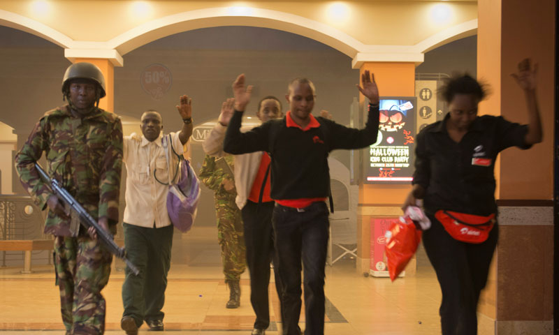 Civilians who had been hiding during the gun battle hold their hands in the air as a precautionary measure before being searched by armed police leading them to safety, inside the Westgate Mall in Nairobi, Kenya Saturday, Sept. 21, 2013. – AP Photo