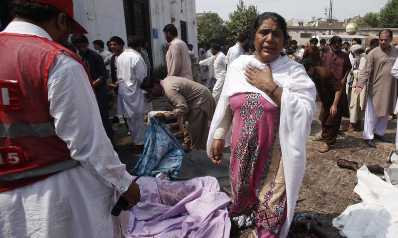 A woman mourns the death of her relatives at the site of a suicide blast at a church in Peshawar September 22, 2013. — Photo Reuters
