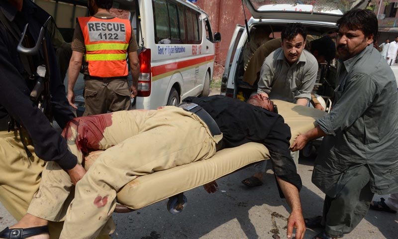 Pakistani men carry an injured policeman into a hospital after two suicide bomb attacks on a Church in Peshawar on September 22, 2013. Two suicide bombers killed at least 53 people and wounded more than 100 in an attack on a church service in the restive northwestern Pakistani city of Peshawar, officials said.  — Photo AFP