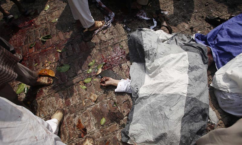A body lies covered on the ground at the site of a suicide blast at a church in Peshawar September 22, 2013. — Reuters Photo