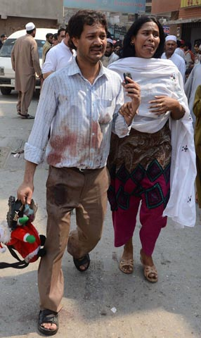 A Pakistani Christian couple react as they arrive at a hospital after two suicide bomb attacks on a Church in Peshawar on September 22, 2013. — Photo AFP