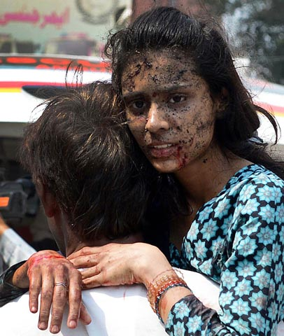 A Pakistani Christian carries an injured woman on her arrival at the hospital after two suicide bomb attacks on a Church in Peshawar on September 22, 2013. — Photo AFP