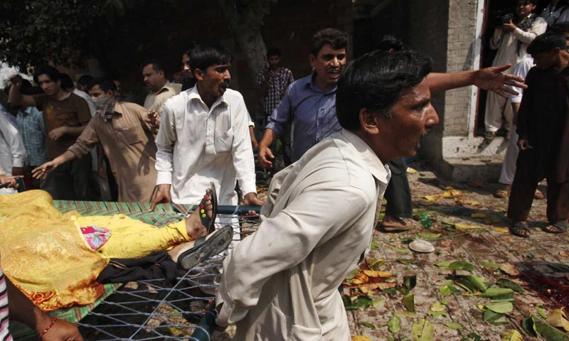 Men carry an injured women on a stretcher at the site of a  suicide blast at a church in Peshawar September 22, 2013. — Photo Reuters