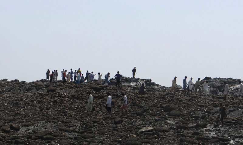 In this photo released by the Pakistani Government, men walk on an island that appeared 2 kilometres off the coastline of Gwadar on September 25, 2013, after an earthquake the day before. —AFP PHOTO/ Pakistan Government