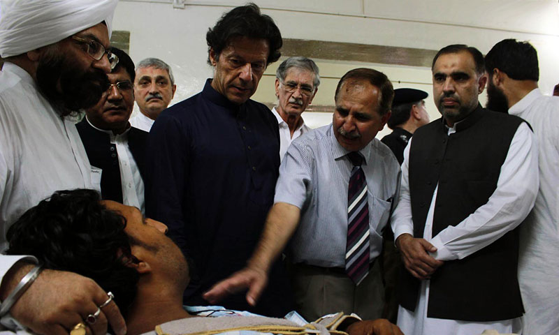 PTI chairman Imran Khan inquiring about the health of twin blast victims at the Lady Reading Hospital in Peshawar. — Online photo