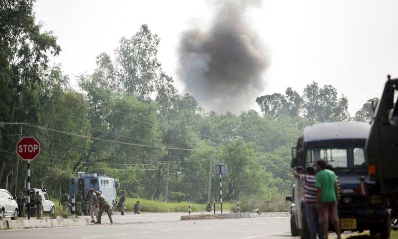 Indian police officials, civilians and army personnel look on as smoke rises during an attack by militants on an army camp at Mesar in Samba district, some 20 kilometres southeast of Jammu on September 26, 2013. — Photo by AFP