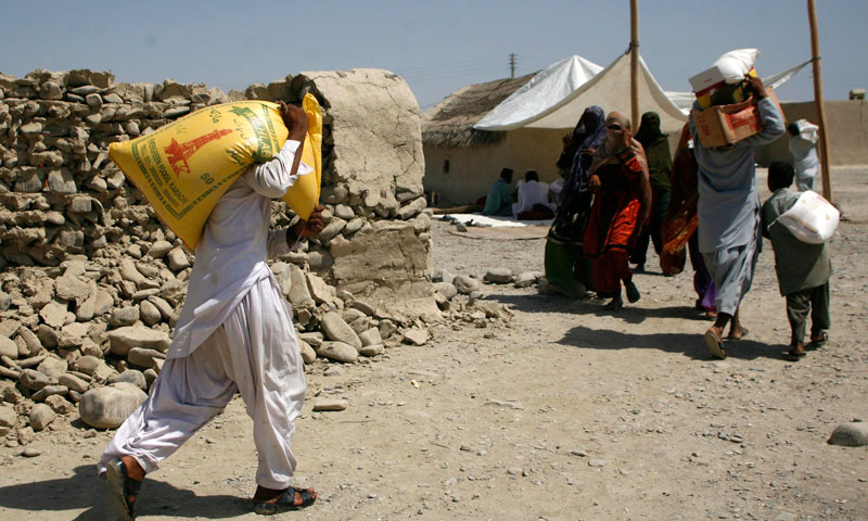 Survivors of an earthquake carry relief goods that were collected from a distribution point in the town of Awaran, Balochistan, September 26, 2013. – Reuters Photo