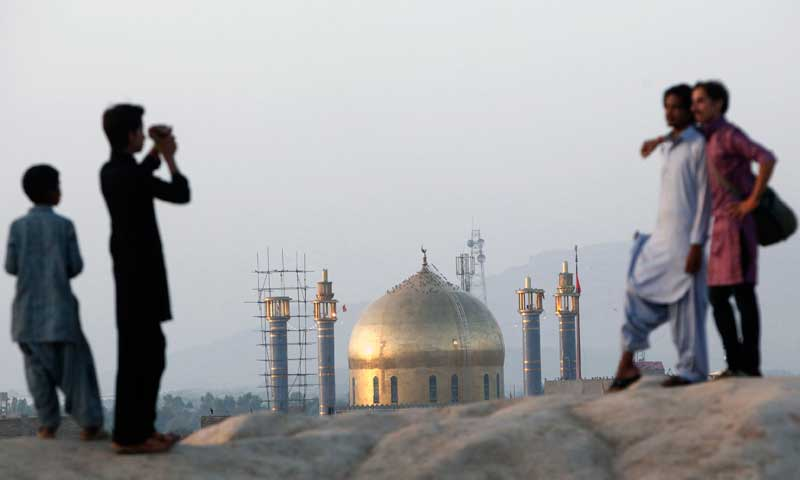 Devotees visiting the tomb of Sufi saint Syed Usman Marwandi, also known as Lal Shahbaz Qalandar, take photographs of each other from an old fort, in Sehwan Sharif, September 6, 2013. — Photo by Reuters