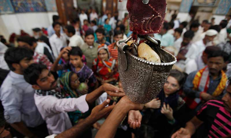 Devotees reach out for sacred water from a carved silver casing in the hallway at the tomb of Sufi saint Syed Usman Marwandi, also known as Lal Shahbaz Qalandar, in Sehwan Sharif, September 5, 2013. — Photo by Reuters