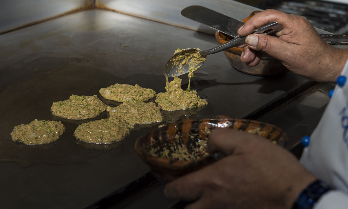 Chef Don Chon cooks a plate with nopal (Cactus leaves) and mosquito eggs in his restaurant's kitchen.