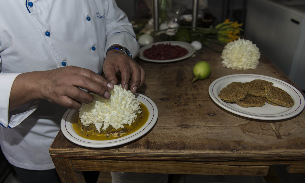 Chief Don Chon serves a plate of ant eggs and chrysanthemums in his restaurant's kitchen.