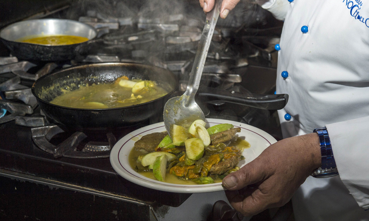 Chief Don Chon serves a plate of small pancakes made with ant eggs, nopal (cactus leaves) and zucchini.