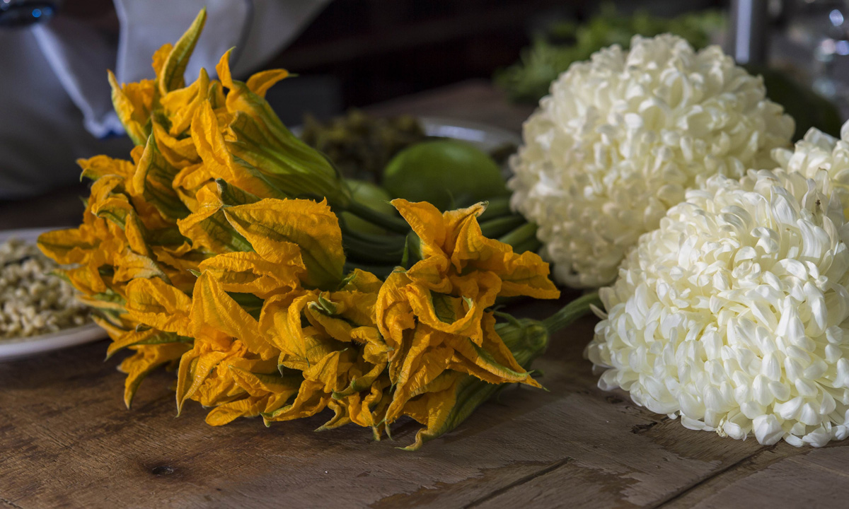 Detail of pumpkin flowers and Chrysanthemums used to prepare plates with mosquito and ant eggs at Don Chon restaurant's kitchen