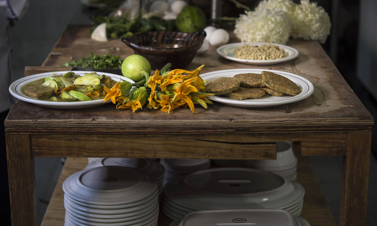 Plates of mosquito eggs with nopal (cactus leaves) with  pumpkin flowers (Left) at Don Chon restaurant's kitchen.