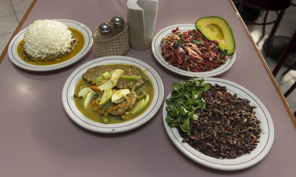 """Plates of ant eggs with chrysanthemums, """"acociles"""" (small crayfish) with avocado and onions, small pancakes of mosquito eggs with nopal (cactus leaves), pumpkin flowers and """"chapulines"""" (Grasshoppers) flamed in mezcal."""