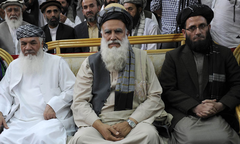 Former Islamist warlord, Abdul Rasul Sayyaf (C) sits with his two vice-presidential candidates, Mohammad Ismail Khan (L) and Abdul Wahab Erfan during a registration process for the forthcoming presidential elections at the Independent Election Commission (IEC) in Kabul on October 3, 2013. – AFP Photo