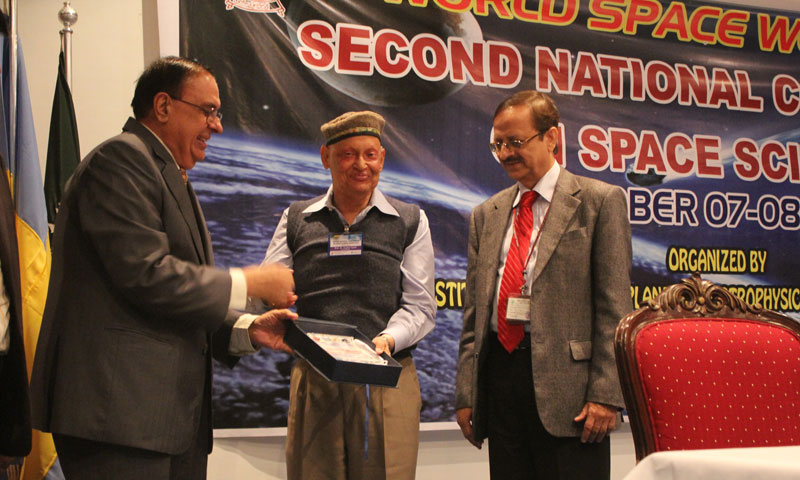 Dr. Atta-ur-Rehman presenting a shield to Pakistan's eminent cosmologist and mathematician Dr. Asghar Qadir at the second National Conference on Space Sciences at Karachi University. — Photo by Muhammad Umar/Dawn.com