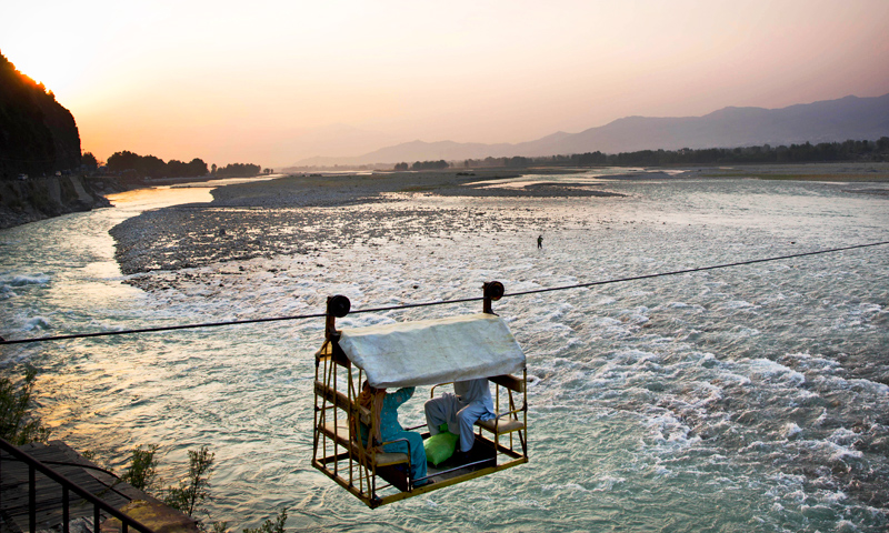 A makeshift chair lift with people on board crosses the Swat river on the outskirts of Mingora, Swat Valley. The chair lift begins across the Swat river near the former headquarters of the Taliban who where driven from Swat in a military operation in 2009. -Photo by AP