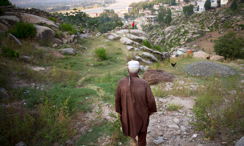 """Farmer Painda Khan, uncle of Attaullah, who is being accused of shooting Malala Yousufzai a year ago, makes his way down from his family house in Ghawari Mastas, Swat Valley, Pakistan. In a rare interview to the AP, Attaullah's uncle, Painda Khan mumbled: """"We don't know why people are blaming him. No one has told us why."""" -Photo by AP"""