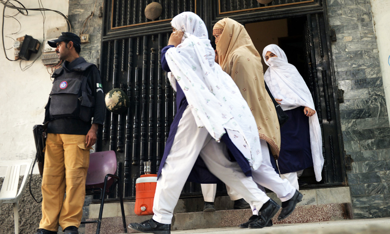 A Policeman stands guard as students leave the school of child activist, Malala Yousafzai in Mingora, Swat. -Photo by AFP