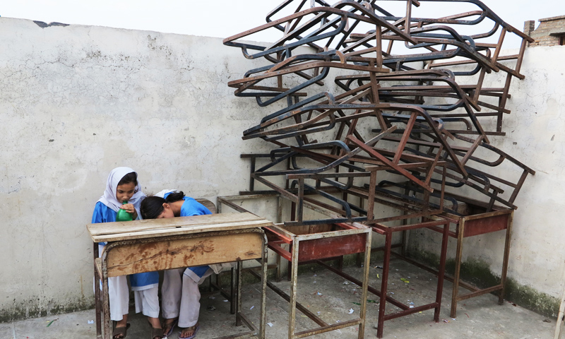 Students sit next to remains of broken benches in a school in Mingora, Swat. -Photo by AP Photo