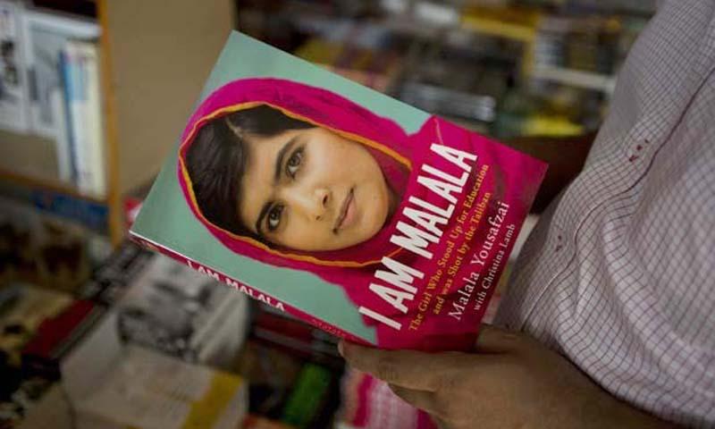"A man holds a copy of Malala Yousafzai's autobiography, ""I am Malala"". — Photo AP"