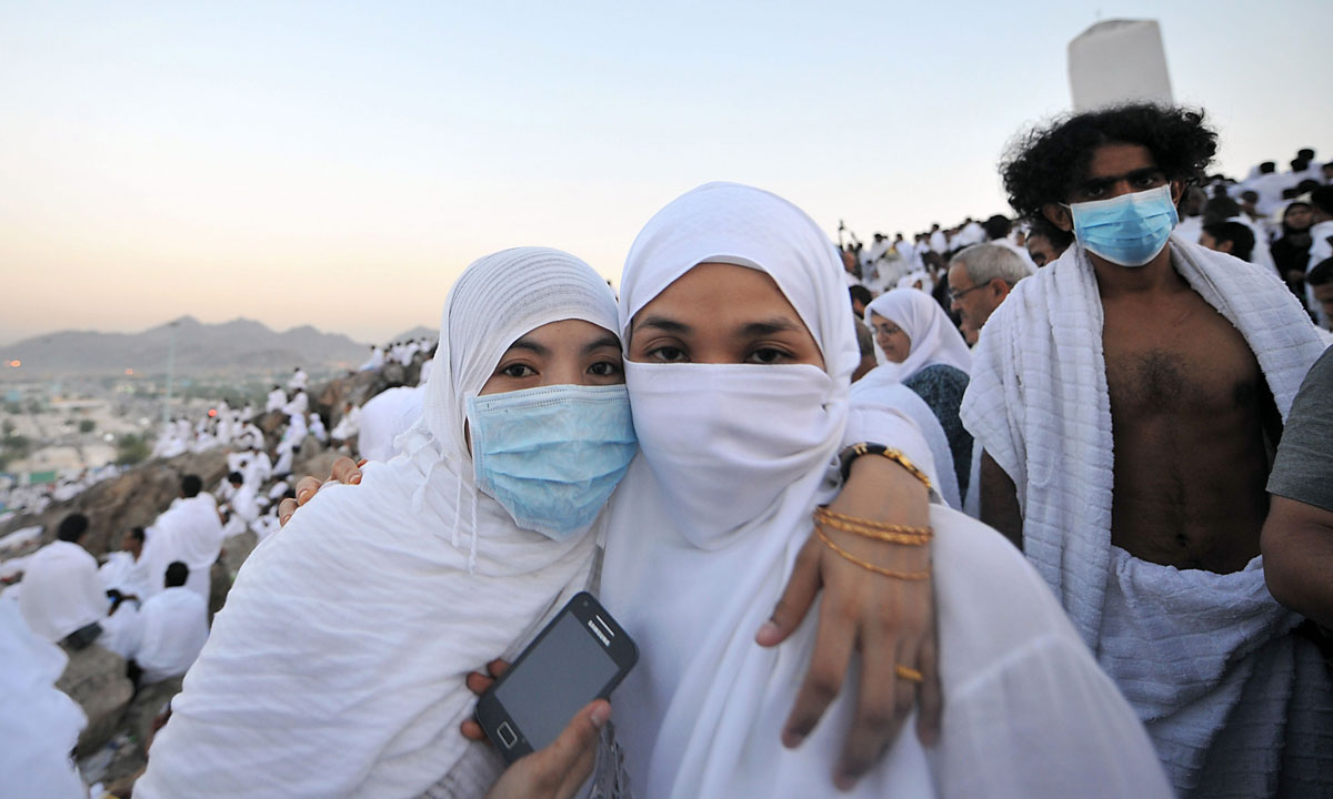Pilgrims pose for a picture on top of Mount Arafat. Many pilgrims have taken to wearing face masks this year to prevent contracting the MERS corona virus. – Photo by AFP