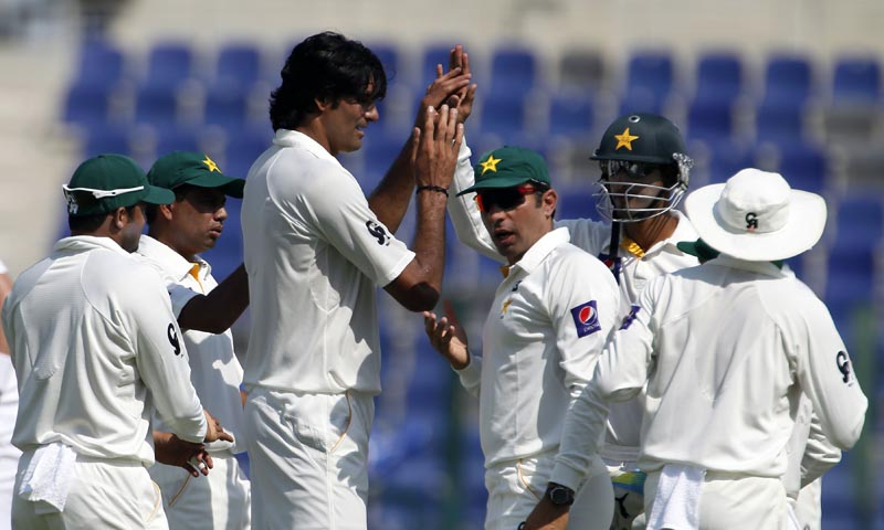 Pakistani cricketers celebrate the dismissal of Hashim Amla of South Africa during the first Test at the Sheikh Zayed Cricket Stadium in Abu Dhabi on October 14, 2013.— Photo by AFP