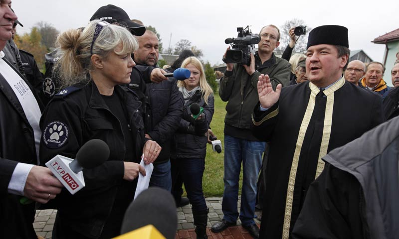 Mufti of Poland Tomasz Miskiewicz (R) speaks to animal rights activists and to reporters gathering outside the mosque in Bohoniki village, eastern Poland. -AFP Photo