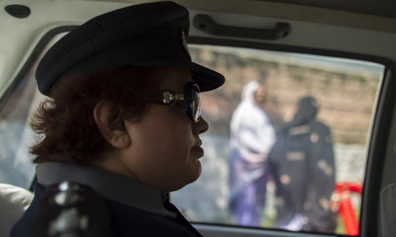 Pakistani Police Inspector Shazadi Gillani (L) drives past women outside a police station in Abbottabad September 18, 2013. — Photo by Reuters