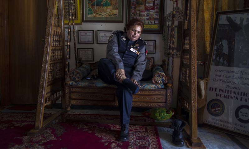 Pakistani Police Inspector Shazadi Gillani removes her shoes at her house in Abbottabad September 18, 2013. — Photo by Reuters