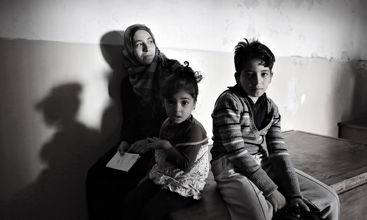 A Syrian mother and her children wait to receive medical help at a recently opened refugee camp sheltered in an old school in the outskirts of the capital Sofia, Saturday, Oct. 19, 2013.  The impoverished Balkan state has seen a considerable refugee influx over the past months, with authorities saying the number of asylum seekers in the country may reach up to 20,000 by the end of the year. - AP Photo