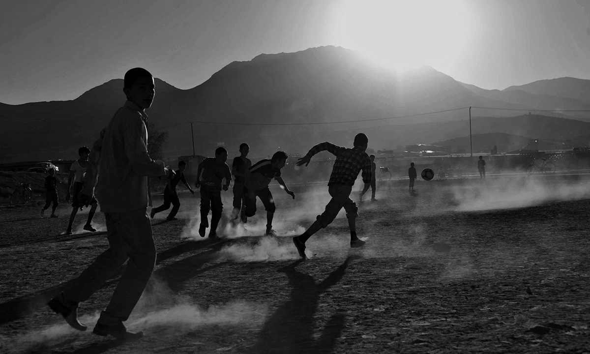 Afghan children play soccer in front of the ruined Darul Aman Palace on the outskirts of Kabul on October 19, 2013.  Nestling beneath the mountains that ring Kabul, the shattered shell of the Darul Aman palace stands in mute testimony to the brutality and callousness of Afghanistan's history of conflict. - AFP Photo
