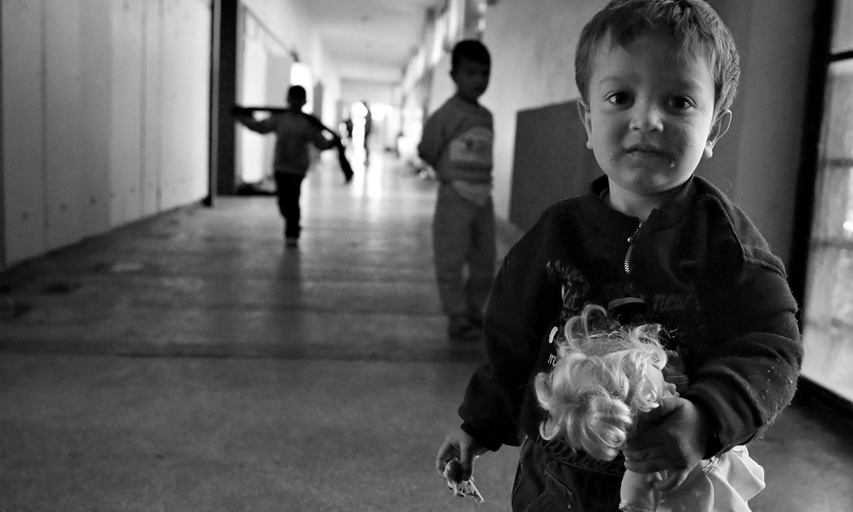 A Syrian boy holds a doll in the corridors of a recently opened refugee camp sheltered in an old school in the outskirts of the capital Sofia. Fears are growing that with deteriorating living conditions of the refugees the situation could soon turn into a humanitarian crisis. - AP Photo