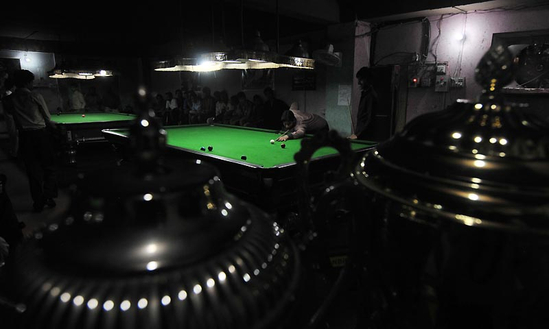 In this photograph taken on September 13, 2013 Pakistani snooker player Mohammad Asif plays at a snooker club in Faisalabad.  — Photo by AFP