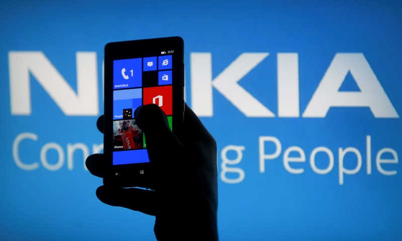 A woman poses with a Nokia Lumia smartphone in this photo illustration in the central Bosnian town of Zenica, May 6, 2013. — Reuters Photo