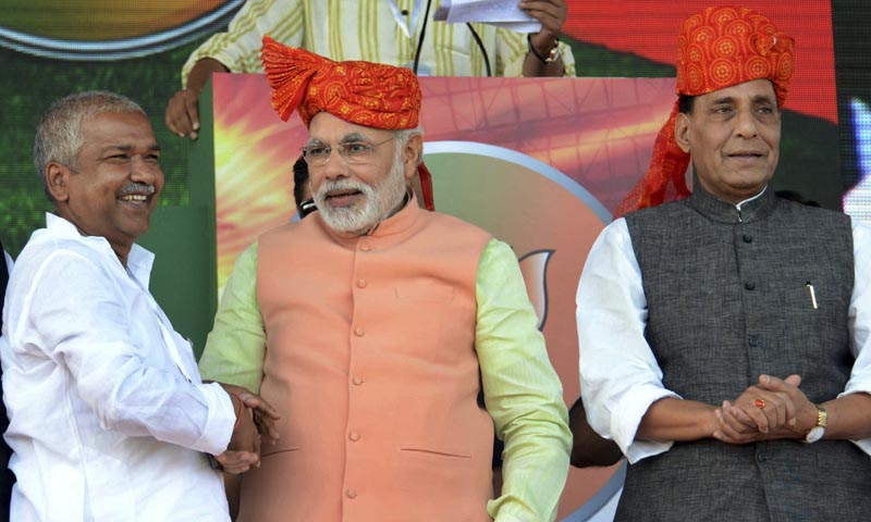 India's main opposition Bharatiya Janata Party's prime ministerial candidate Narendra Modi shakes hands with a supporter as he stands next to party president Rajnath Singh, right, at a rally in Patna, Oct 27, 2013. — Photo by AP