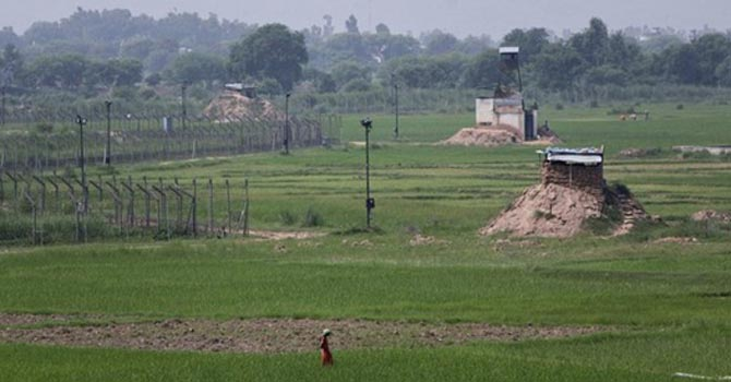 A farmer works in a paddy field near the fenced border between Indian and Pakistan.   — File Photo by Reuters