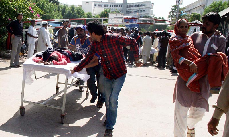 Rescue workers shifting the women workers who went unconscious after leakage of poisonous gas in a factory in Export Processing Zone in Landhi Area.— Photo by Online