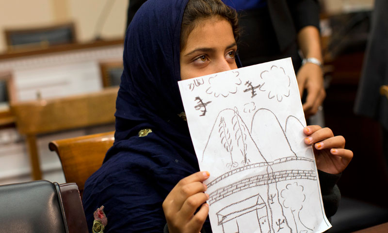 Nine-year-old Nabila Rehman holds a photo with a drawing she made depicting a drone strike that killed her grandmother, Tuesday, Oct. 29, 2013, during a news conference on Capitol Hill in Washington. – AP Photo