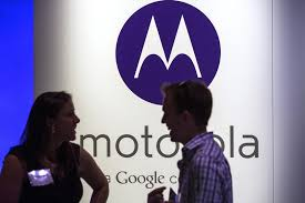 A man and woman laugh in front of a Motorola logo at a launch event for Motorola's new Moto X phone in New York, August 1, 2013.— Reuters Photo